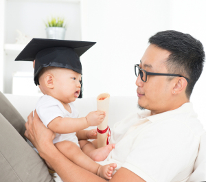 Asian family lifestyle at home. Baby with graduation cap holding certificate. Child and father early